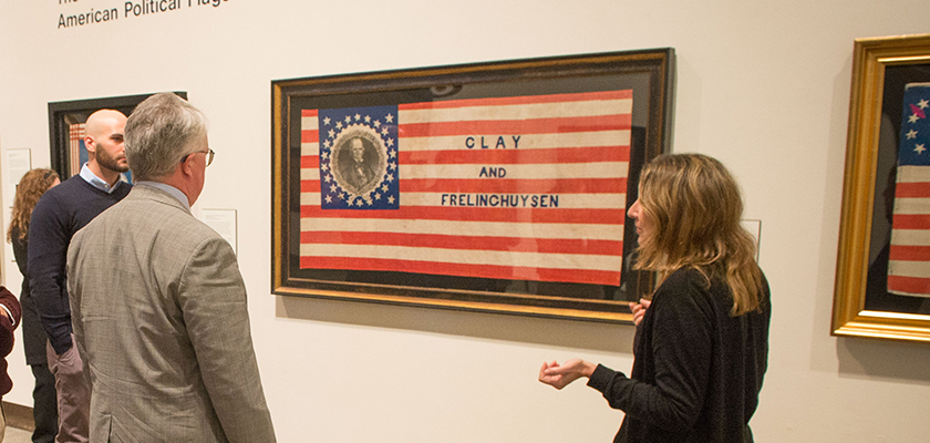 Nancy Stula, executive director, leads state legislators and aides on a tour of the Mark and Rosalind Shenkman Collection of American Political Flags and Textiles on display at the William Benton Museum on Dec. 16, 2016