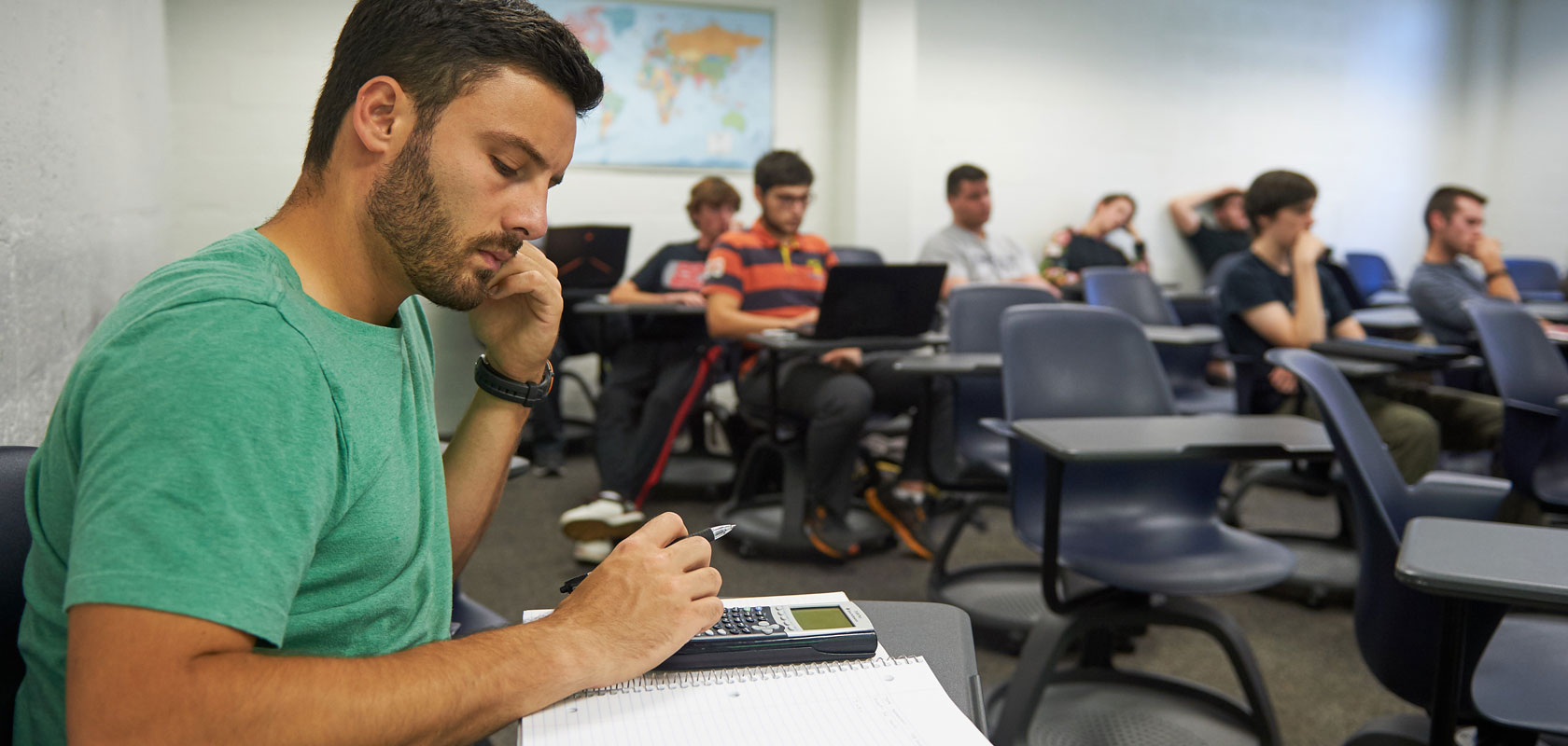 A student uses a calculator during a lecture at the Avery Point Campus