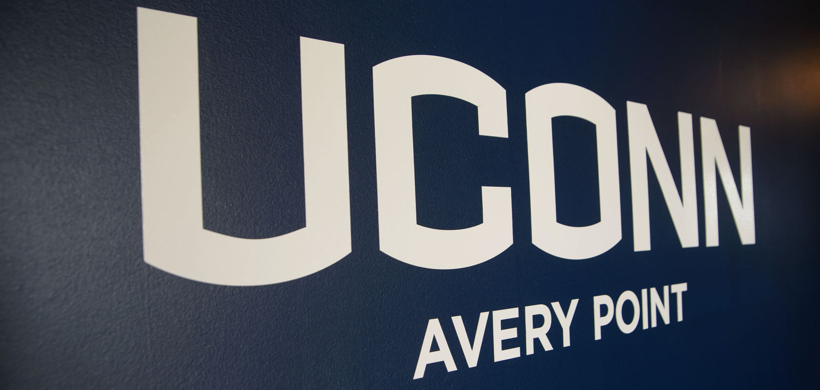 UConn Avery Point logo on a blue wall
